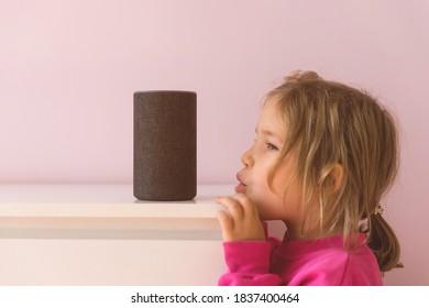 sprachgesteuerter intelligenter Lautsprecher. Kleines Kind, das mit Amazon Alexa Echo Dot spricht. Bildungsprogramm für Kinder. Junge Mädchen spricht mit Alexa und gibt es Befehle und Befehle, was zu schalten.