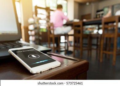 Voice recognition , speech detect and deep learning concept. Application on mobile phone screen in coffee shop background with flare light effect