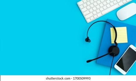 VOIP Helpdesk headset, keyboard computer notebook and mouse isolated on blue background. Communication support for callcenter and customer service Helpdesk