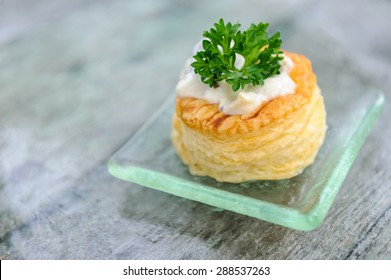 A vol-au-vent canape on a glass plate, decorated with a sprig of parsley.