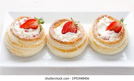 Vol-au-vents with strawberries, cream and mascarpone. Puff pastry stuffed with soft mascarpone cream and with strawberries on a white plate. French dessert Volovany.