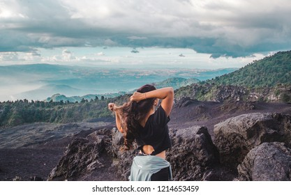 Volcan Pacaya, Guatemala - 25 Aug 2018: Young female traveller flicks hair at the top of Pacaya Volcano, looking over volcanic rock and a lush valley
