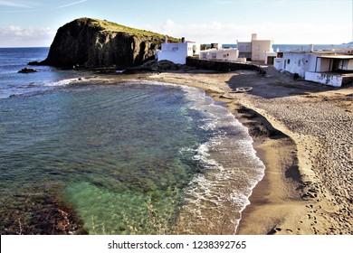 Volcanic cliffs from beach in the village of Isleta del Moro, Cabo de Gata Natural Park, Almeria, Andalusia, Spain, tourism, tourist, advertising, travel, traveler, holidays, tourist destination,