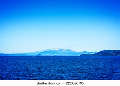 Volcanic cones of Ruapehu towering over great lake of Taupo on a beautiful sunny day. North Island Volcanic Plateau, New Zealand