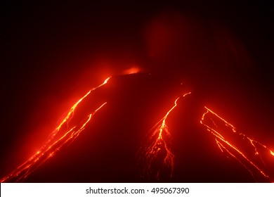 Volcanic erupting landscape of Kamchatka: night eruption Klyuchevskaya Sopka, glowing red hot lava flows on slope of volcano. Russian Far East, Kamchatka Peninsula, Klyuchevskaya Group of Volcanoes.