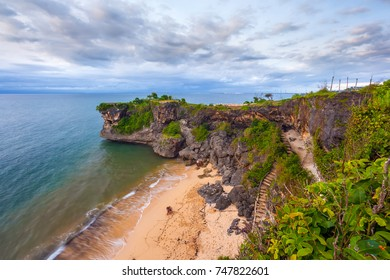 Volcanic green rock with huge stones and stair, on the sea shore against the backdrop of beach sunset. Beautiful blue clouds on the horizon.