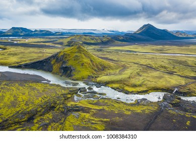 Volcanic hills protrude from mossy field in Iceland