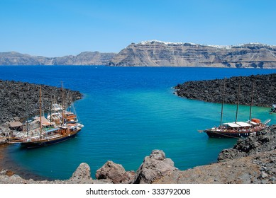 Volcanic island and bay with view of Fira, Santorini in the background