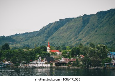 Volcanic Island of Samosir on the lake of Toba, on northern Sumatra, Visible typical houses and christian church on the island on a cloudy day.