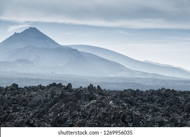 volcanic landscape after eruption with black lava field and volcano mountain in haze, Lanzarote, canary islands, Spain, Europe