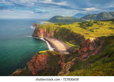 Volcanic landscape with green plains and rocky coast on Kamchatka peninsula, Russia