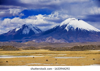 Volcanic landscape with snow capped Parinacota volcano and cloudy sky in Lauca National park, Chile.