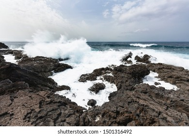 Volcanic lava coastline in the south of La Palma, Spain near the lighthouse and salinas of Fuencaliente with tall waves.