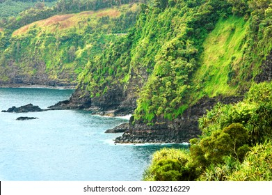Volcanic rock cliffs fall off into the Pacific Ocean near Hana, Hawaii on the Island of Maui making a dramatic cliff at the waters edge.