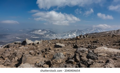 Volcanic rocks are scattered along the mountainside, devoid of vegetation. In the distance, against the background of blue sky and clouds, you can see mountains with snow-covered slopes. Kamchatka.