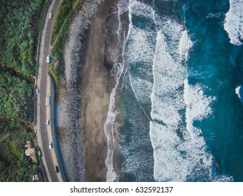 Volcanic sunset beach in Tenerife, Benijo. Paradise beach in Canary Island. Flight above ocean waves, washing up on a black volcanic sand beach. Aerial shot of tide, sea, wide dramatic landscape view