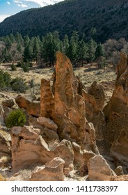 Volcanic tuff rock formations along the main loop trail with the Tyuonyi Pueblo ruins in the background at Bandelier National Monument, NM