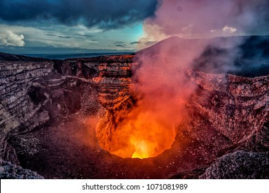 Volcano crater eruption with flowing lava and smoke.  The Masaya Volcano near Managua, Nicaragua main crater after sunset.