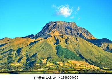 Volcano Imbabura with green fields on the side and a small cloud at the peak in Cotacachi, Ecuador