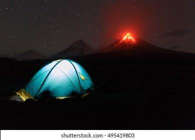 Volcano landscape of Kamchatka Peninsula: night view of illuminated tourist tent under night sky, stars and background eruption Klyuchevskoy Volcano. Russian Far East, Klyuchevskaya Group of Volcanoes
