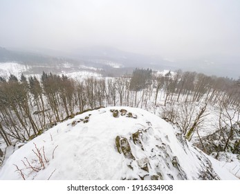 Volcano rock formation Zlaty vrch built pentagonal and hexagonal basalt columns. Looks like giant organ pipes. Covered by snow and ice in winter time - Shutterstock ID 1916334908