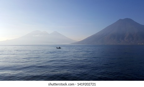 Volcanoes skyline in-front of Lake Atitlan, Guatemala with local man paddling traditional boat silhouetted against the water