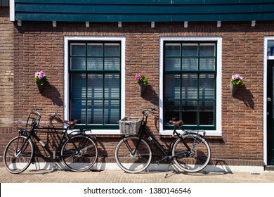 Volendam / Holland - April 21 2019: two bikes brand Sparta parked in front of the building build in traditional dutch style. Dark brown bricks, large windows. Cozy atmosphere of small town Volendam