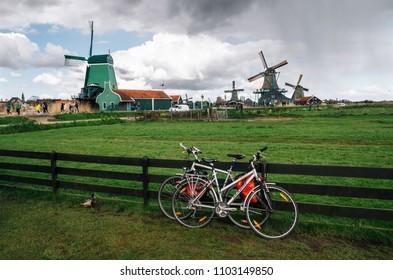 Volendam, Netherlands - 26 April, 2017: Bicycles parked close to fence against authentic Zaandam mills in Zaanstad village on the river Zaan Landmark of Netherlands.