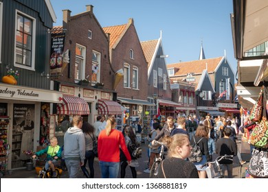 Volendam, Netherlands - April 7, 2019: View of the fishing village of Volendam and a main shopping street in the harbour. People enjoying beautiful sunny spring day on a promenade