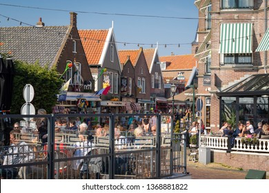 Volendam, Netherlands - April 7, 2019: View of the fishing village Volendam in the Netherlands.  People enjoying beautiful sunny spring day in restaurants on a main shopping street in the harbour.