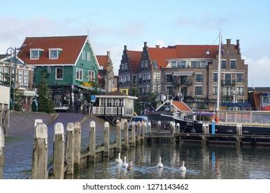 VOLENDAM, NETHERLANDS - DEC 11, 2018 - Swans swim in the Marina and waterfront of Volendam, Netherlands