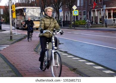 VOLENDAM, NETHERLANDS - DEC 11, 2018 - Bicyclists on a bike path in the fishing village of Volendam, Netherlands