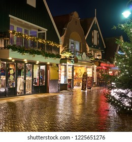 Volendam, Netherlands - December 31, 2018: Downtown of Volendam is decorated with Christmas and New Year illuminations. Deserted pre-Christmas street of the old town on a winter night in the rain