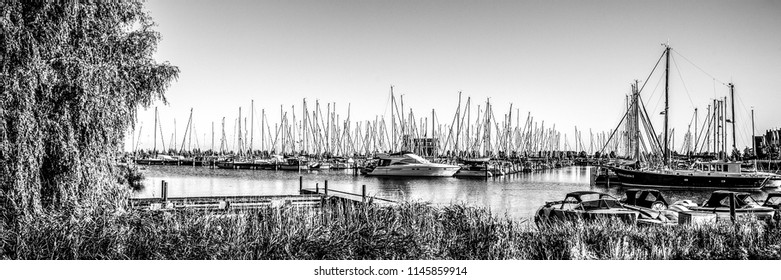 VOLENDAM, NETHERLANDS - JUNE 18, 2014: Boats and sail boats in Volendam Harbor. Volendam - a small town that has preserved the tradition of Dutch fishing villages. Panorama.