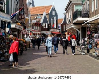 Volendam, Netherlands - June 3, 2019: the main street of Volendam with tourists and souvenir shops.