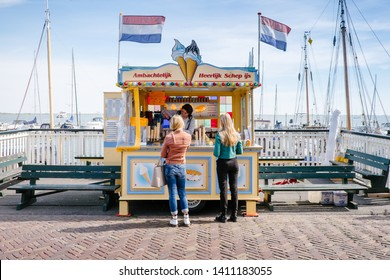 Volendam, Netherlands - May 14, 2019: two people in front of the kiosk selling ice cream along the Volendam marina
