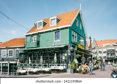 Volendam, Netherlands - May 14, 2019: typical Dutch pub with people sitting outdoors overlooking the marina of Volendam