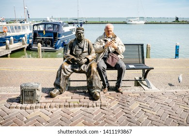Volendam, Netherlands - May 14, 2019: gentleman sitting on the bench using the mobile phone next to the statue located along the marina of Volendam