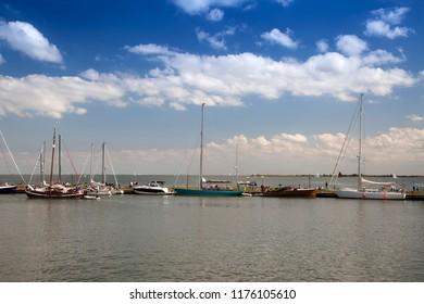 VOLENDAM,HOLLAND,NETHERLANDS -AUGUST 19, 2018:Boats at the harbor entrance of the small harbor of Volendam, Markermeer, Holland, Netherlands