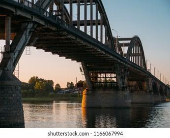 Volga bridge and embankment over Volga river at sunset, Yaroslavl region, Rybinsk city, Russia. Beautiful landscape with water