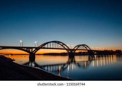 Volga bridge over Volga river after sunset with reflection in water, Yaroslavl region, Rybinsk city, Russia. Beautiful night or evening landscape