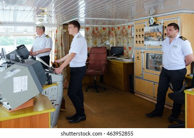 """VOLGA RIVER, RUSSIA - JULY 19, 2016: Captain of river cruise ship """"Alexander Benois"""" and mates of captain in captain's cabin"""