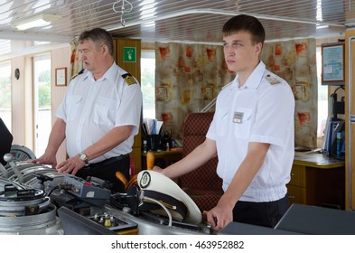 """VOLGA RIVER, RUSSIA - JULY 19, 2016: Captain of river cruise ship """"Alexander Benois"""" and assistant to captain in captain's cabin"""