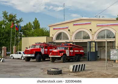 VOLGOGRAD - AUGUST 29: Fire trucks are in full readiness on the ground in front of the fire station with old fire tower. August 29, 2015 in Volgograd, Russia.