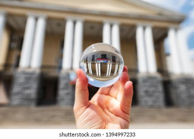 VOLGOGRAD - MAY 4: The building of the Volgograd musical theater with large columns at the entrance. Photo taken through an optical ball. May 4, 2019 in Volgograd, Russia.