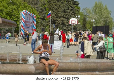 VOLGOGRAD - MAY 4:Participant of the Volgograd marathon takes  plate number with t-shirts sitting at the fountain of Arts.  May 4, 2014 in Volgograd, Russia.