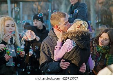 Volgograd, Russia - April 01, 2011: Kissing couple on a flashmob of soap bubbles in Volgograd