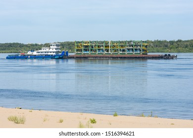 Volgograd, Russia - August 27, 2019: Transportation by a tugboat of a floating platform with technological equipment