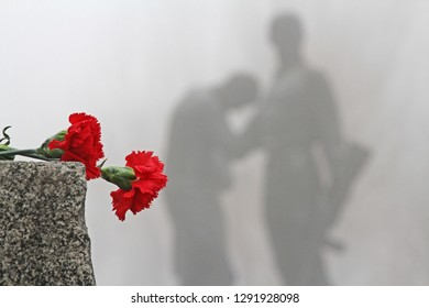 Volgograd, Russia - February 03, 2013: Red carnations lie on a granite cobblestone on the background of the monument to Komsomol members in Volgograd.