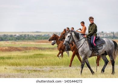VOLGOGRAD, RUSSIA - JUNE 8: Young guys and girls ride in the field on their horses. June 8, 2019 in Volgograd, Russia.